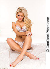sexy blonde woman sitting on white bed