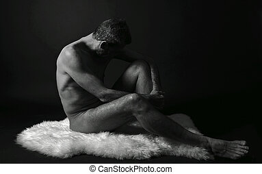 nude man sitting in front of black background