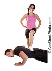 Woman stepping on man pushups - W couple is working out The...