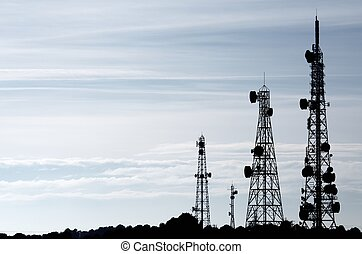 telecommunications towers - silhouette of a group of...