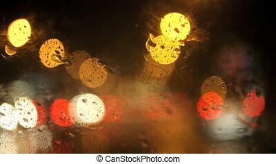 Rain drops on the driving car glass by night with blured...