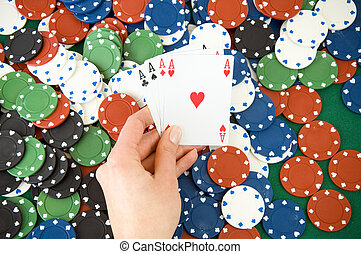 Gambling chips and cards - Four aces in hand, playing cards...