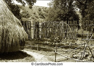 Thatched hut and garden in black and whiteold style sepia...