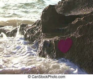 red heart against rock in sea - red heart against rock been...