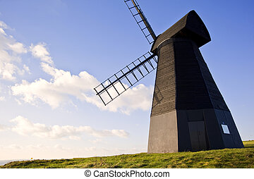 Old wooden smock windmill landscape against vivid blue sky with