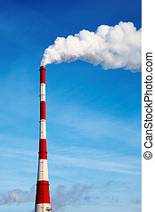 Air polluting smokestack against blue sky