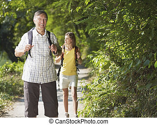 grandfather and grandaughter hiking in wood - senior man and...