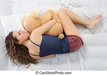 Young woman with teddybear - Young woman sleeping on a bed...