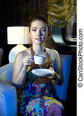 woman drinking tea in restaurant - young beautiful woman...