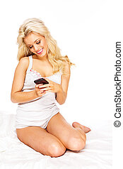 using smartphone - blond woman sending a text message using...