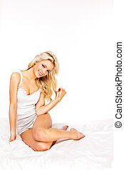 Young happy smiling woman waking up at bedroom. studio shoot