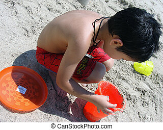 Kid Playing with sand and toys at the beach - Kid laying...