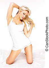 Young happy smiling woman waking up at bedroom studio shoot