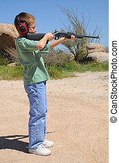Young boy shooting a rifle