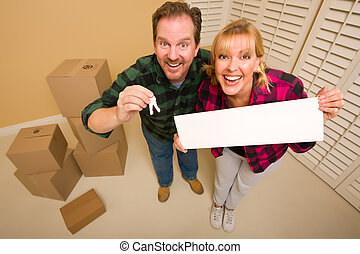 Goofy Couple Holding Keys and Blank Sign Surrounded by Boxes