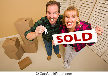 Goofy Couple Holding Key and Sold Sign Surrounded by Boxes