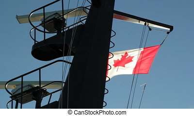 Canadian flag on ship - Canadian flag backlit by the sun,...