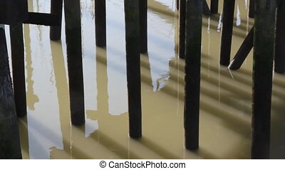 Dock supports. - Large wooden dock supports and brown water.