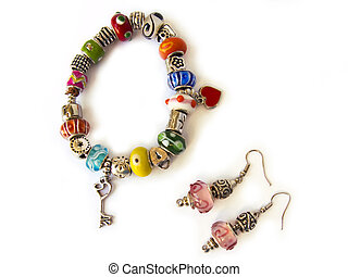 Beads and gems bracelet, and a pair of earrings, isolated in...