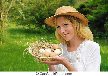Young woman holding fresh eggs