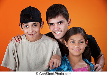 Smiling Siblings - Smiling brothers and sister on an orange...