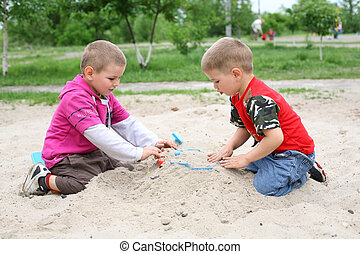 The boys in the sandbox - In the sandbox, boys buried the...