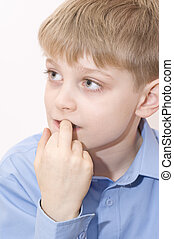 Portrait of young boy biting his fingernails