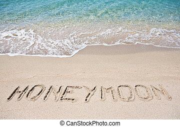Honeymoon written on the sand