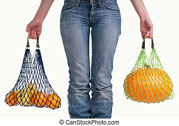 Close up of a woman with jeans carrying yellow fruits -...