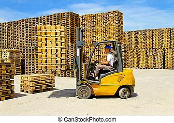 Forklift handling - Forklift operator handling wooden...
