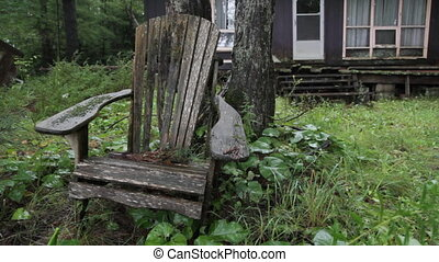 Rainy chair Two shots - A spooky wooden chair sits out in...