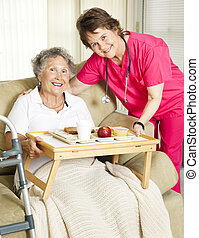Senior Home Meal Delivery - Caring nurse brings meal to...