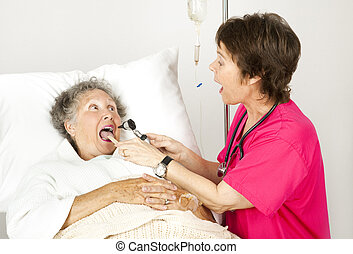 Hospital Nurse - Say Ah - Hospital nurse uses and otoscope...
