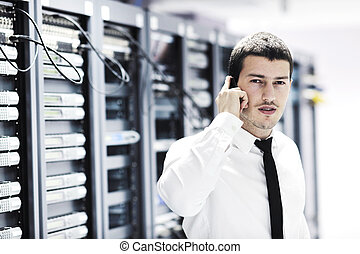 it engineer talking by phone at network room - young...