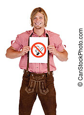 Smiling Bavarian man in lederhose holds non-smoking-rule...