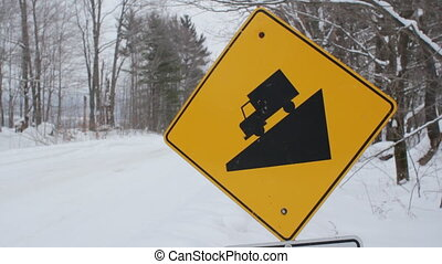 Steep hill sign. Winter. - Yellow, diamond shaped sign warns...