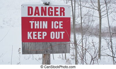 Danger Thin Ice - Sign warns of thin ice Light snow falling...