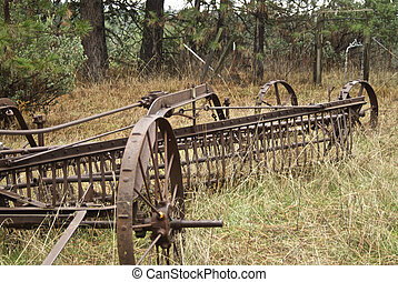 Rusty Hay Rake - An antique hay rake sits rusting in a field