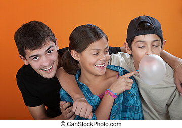 Young girl Touching a bubble from her brothers chewing gum -...