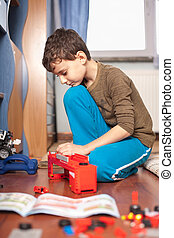 Boy playing with toys - Kid playing with toys indoor, in his...
