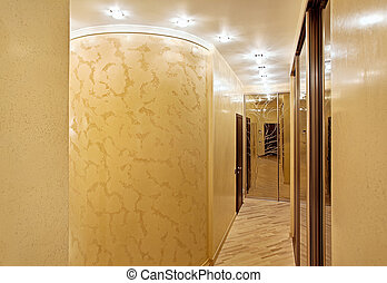 Passage with a mirror wardrobe and column in warm tones