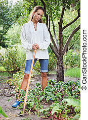 Thoughtful young woman with hoe working in the garden bed