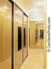 Passage with a mirror wardrobe in warm tones