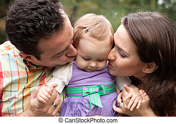 Kiss of love - parents with their baby girl - Kiss of love -...