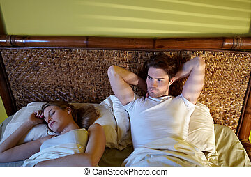 young couple sleeping in bed - caucasian heterosexual couple...