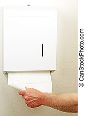 Towel Dispenser - A hand is pulling down and out a white...