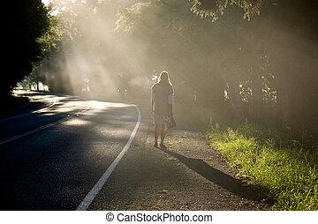 Misty Road - Woman roaming down a misty road.