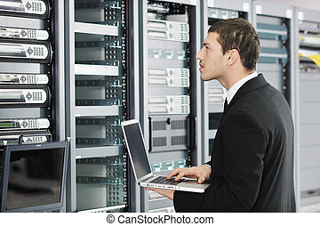 businessman with laptop in network server room - young it...