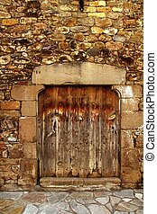 Aged wood door in medieval masonry Pyrenees