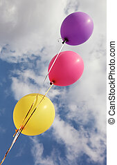 Three vivid color balloons on blue sky background